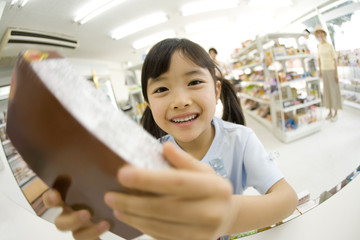 girl holding sweets in convenience store