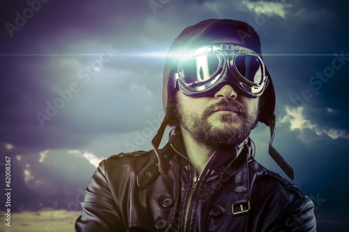 Flight, man dressed as pilot in helmet on clouds background. Vin