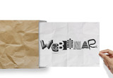 hand pulling crumpled paper from envelope with design word WEBIN