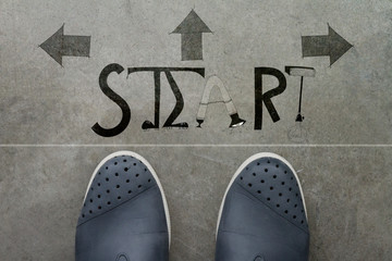 a pair of feet on cement floor print of design word START for th
