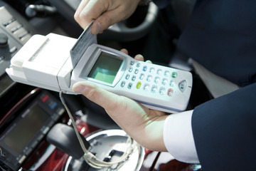 hand of taxi driver paying fo fares by credit card