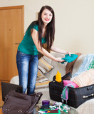 Smiling brunette woman packing suitcase