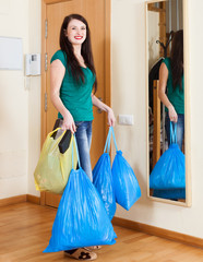 Happy  woman near door with garbage