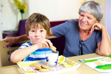 Happy child having snack during homework with smiling grandma