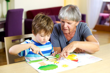 Happy grandmother doing homework with grandson