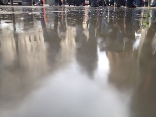 people reflect in wet street in london