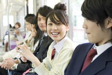 female high scool student sitting on seat of train and shows smiling face