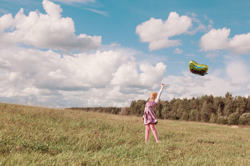 little girl plays with balloon in grass