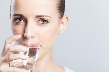 Young curly haired woman drinking water.