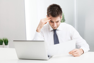 Businessman confused and Scratching Head, with Laptop.