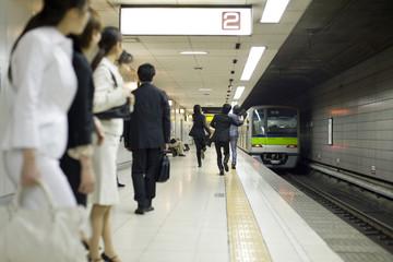 businessman running after train on the platform