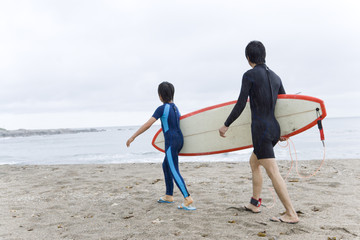 parents and child walking along sandy beach with surfboard