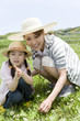 parents and child squating down in grassy field and looking at the camera