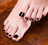 Beautiful women legs with black pedicure after Spa procedures
