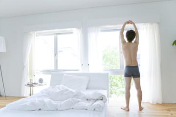 man in underwear doing stretch by window