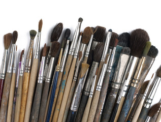 Assorted dirty old painting brushes. Isolated on white