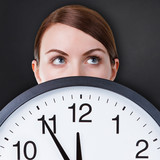 Woman face with a big clock against black chalkboard background