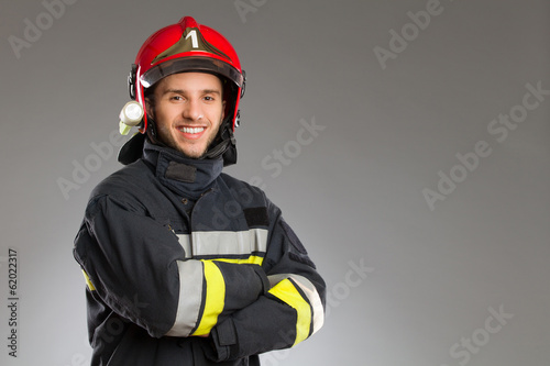 Leinwanddruck Bild Cheerful firefighter with crossed arms.