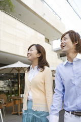 smiling couple walking in front of café