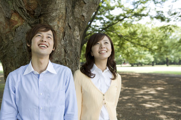 smiling couple standing still under the tree