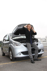 A man standing in front of a stalled car breakdown