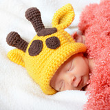 cute baby sleeping in funny yellow giraffe hat and smiling in sw