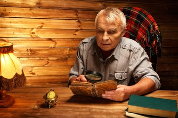 Senior man with magnifier reading vintage book