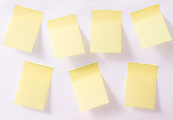 seven yellow pieces of paper on white background