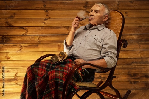 Senior man with smoking pipe sitting on rocking chair - 62024369