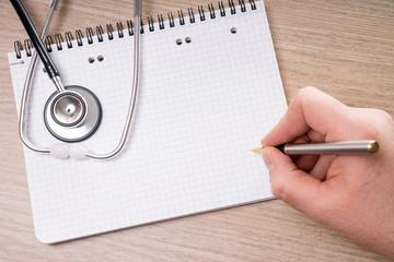 leerer Schreibblock mit Stethoskop auf einem Tisch