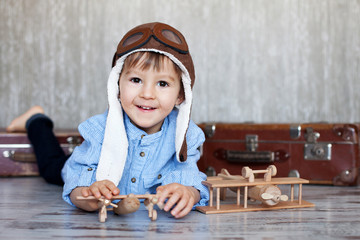 Little boy, playing with wooden plane