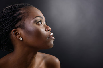 Beautiful young african woman looking up into the corner, face w