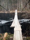 Hanging wooden bridge over a river on forest background