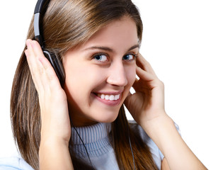 attractive teen girl listening to music on headphones and winkin