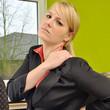 Frau im Büro mit Nacken-Schmerz