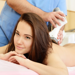 young beautiful woman getting massage therapy on back in beauty