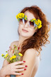 Beautiful young woman with sunglasses, adorned with flowers