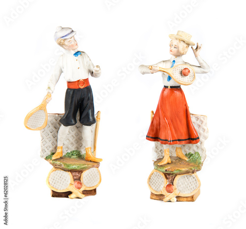porcelain dolls playing tennis over white background
