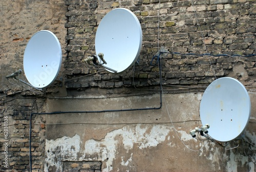 Satellite dish antenna on the old house wall