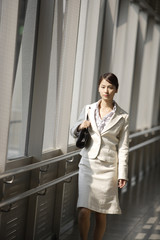 young business woman walking along inside station