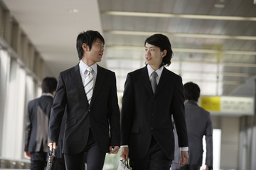 businessman walking along inside station