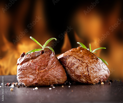 Fresh beef steaks on black stone and fire