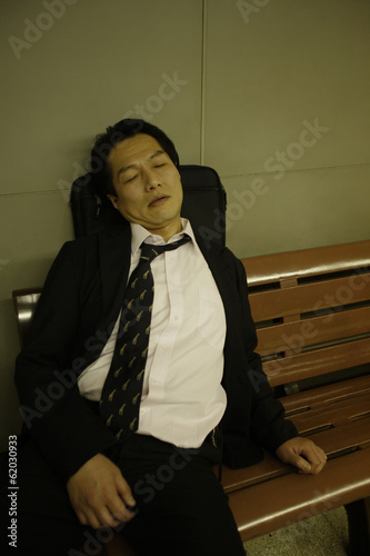 businessman having a nap on bench