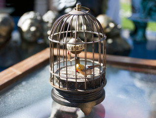 Clock with yellow bird pecking in a cage