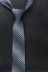 Men's tie lies on the natural leather
