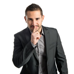 Young man making silence gesture over isolated white background