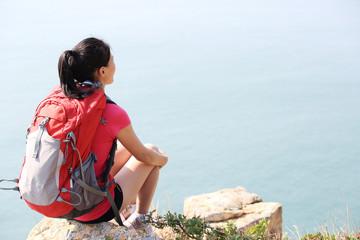 hiking woman sit rest on seaside rock enjoy the view