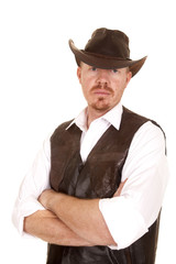 Cowboy in vest and hat arms folded looking serious