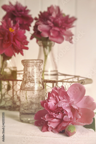 canvas print picture Beautiful peony flowers with bottles on table