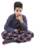 Little child wearing pajamas using asthma inhaler